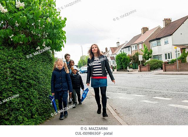 Childminder walking children to school