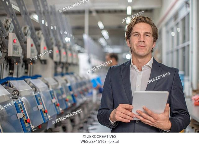 Portrait of confident businessman with tablet in factory