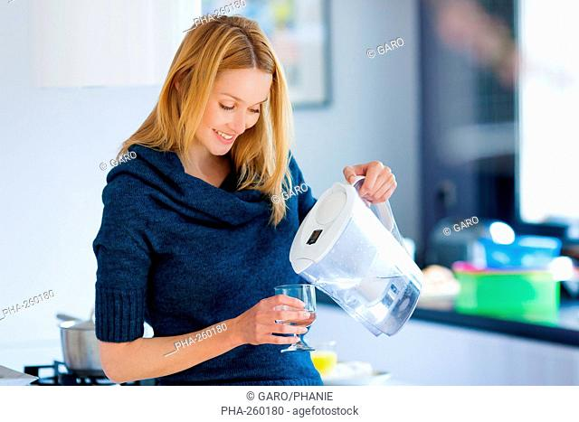 Woman pouring water with filtering pitcher
