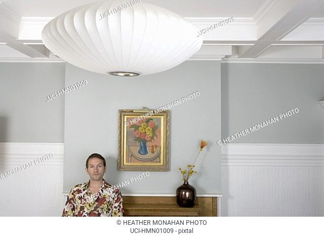 Man standing before fireplace
