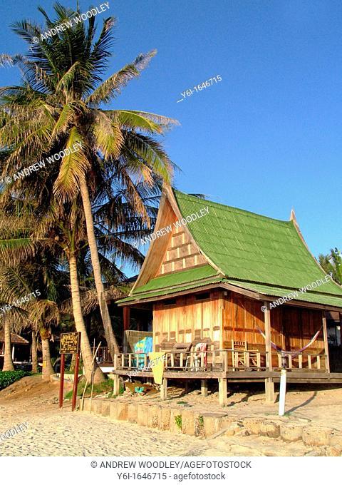 Palm tree and wooden bungalow Sunrise Beach Ko Pha Ngan island Thailand