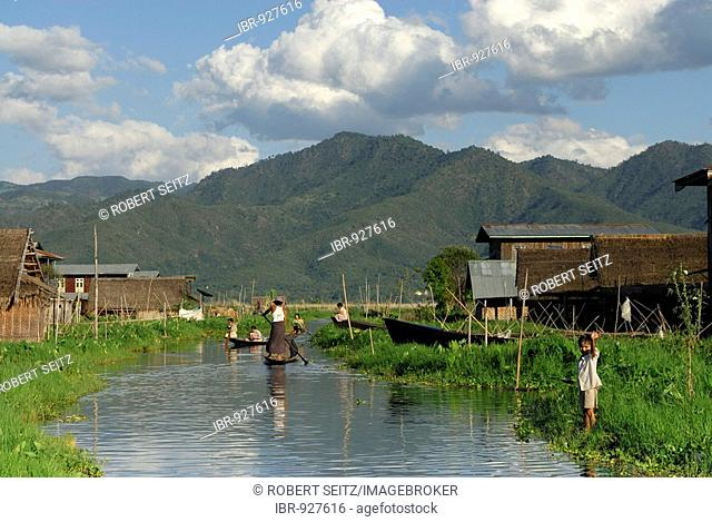 Burmese with boat and waving child, Inle Lake, Myanmar, Burma, South East Asia