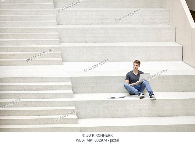 Young man sitting on stairs using laptop