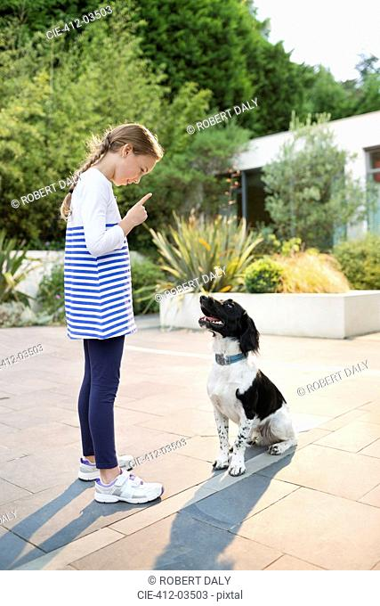 Girl scolding dog outdoors