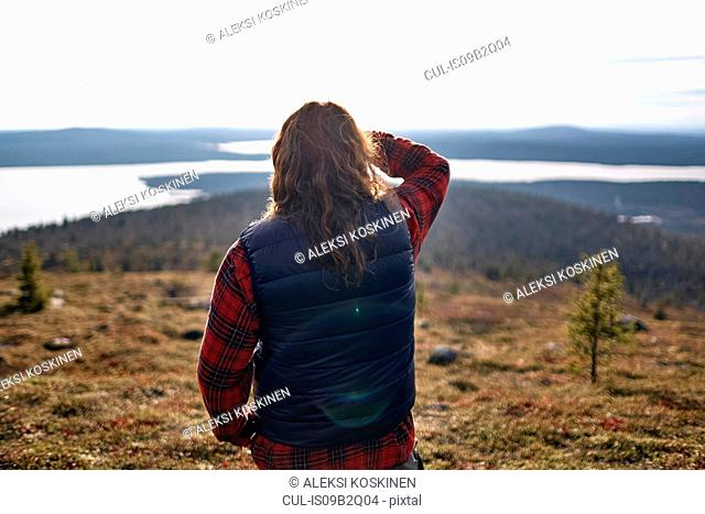 Hiker looking out to lake, Keimiotunturi, Lapland, Finland