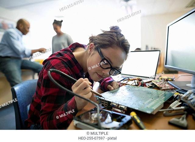 Focused high school student assembling circuit board