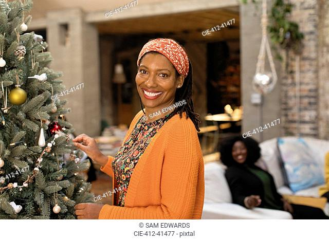 Portrait smiling, confident woman decorating Christmas tree