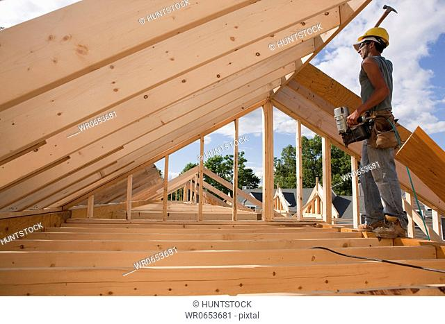 Carpenter hammering on roof rafters