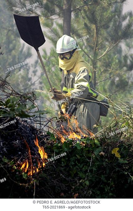 A fire brigade off with a shovel in a forest fire in a forest of Galicia