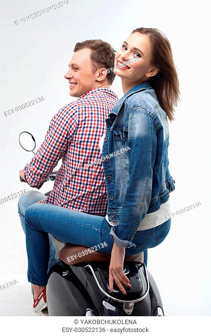 Portrait of cheerful young loving couple sitting on motorcycle. The woman is looking back at the camera and smiling. Isolated