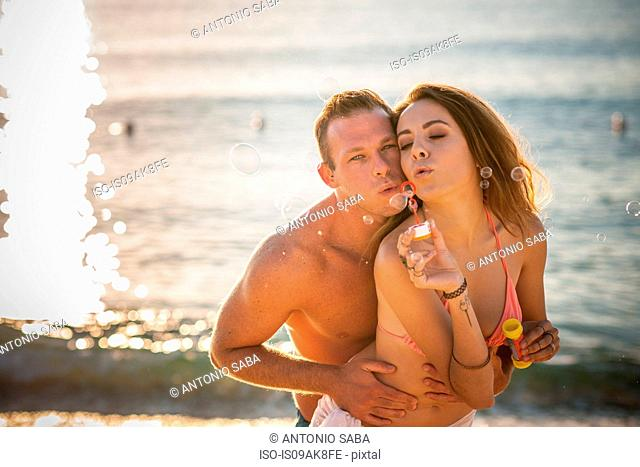 Young couple blowing bubbles on beach, Castiadas, Sardinia, Italy