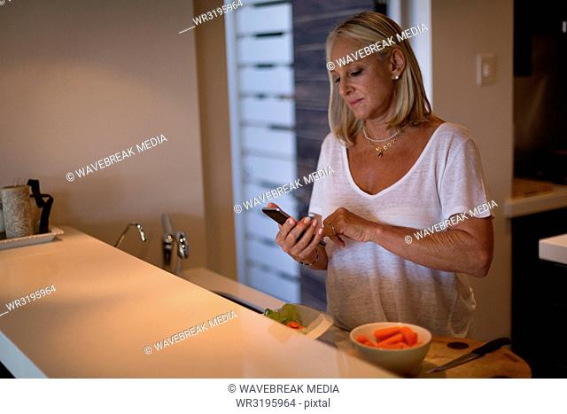 Disabled woman using mobile phone in kitchen
