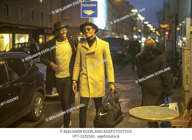 streetstyle, night, two man walking on pavement, street, city, Munich, Germany