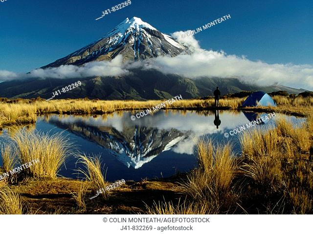 Camping beside tarn reflecting Mt Egmont / Taranaki on the Pouakai Range Egmont National Park New Zealand