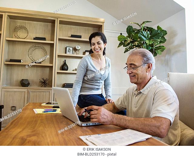Older couple using laptop in home office