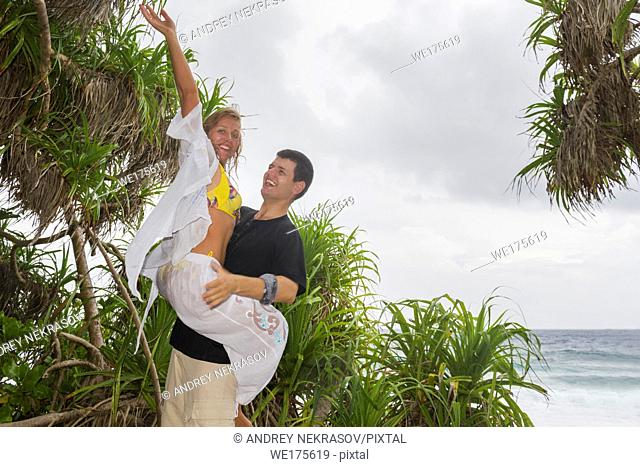 Happy young couple on a beautiful tropical beach. Honeymoon on an exotic island. Honeymoon beautiful couple on an exotic beach