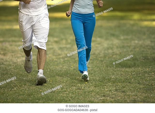 Couple jogging in meadow
