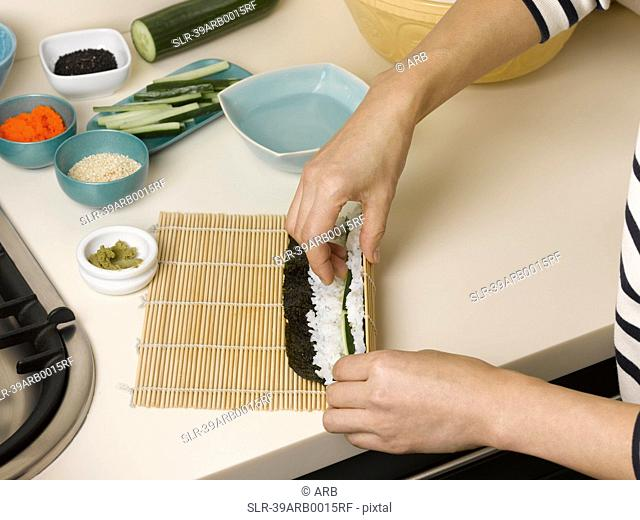 Woman rolling sushi at table