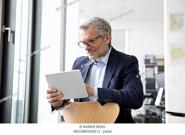 Successful businessman in his office using digital tablet