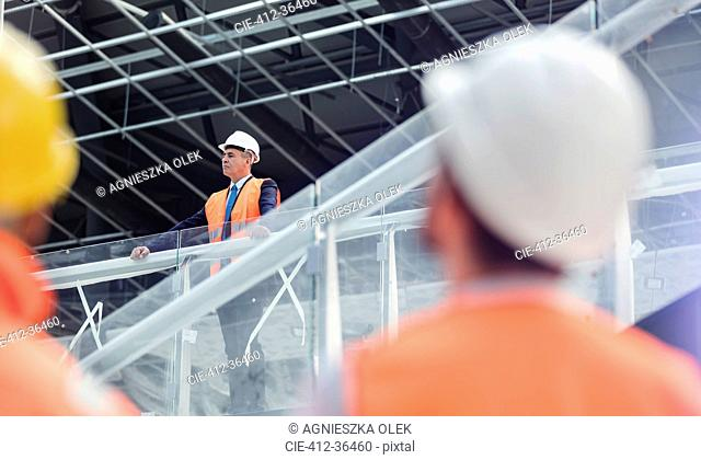 Businessman in hard-hat looking over construction site