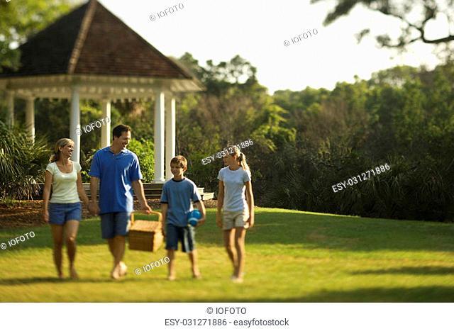 Caucasian family of four carrying picnic basket walking through park