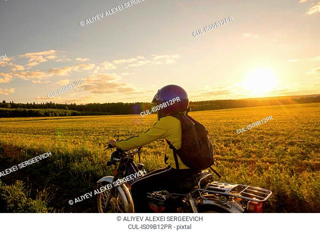 Boy riding bicycle through field