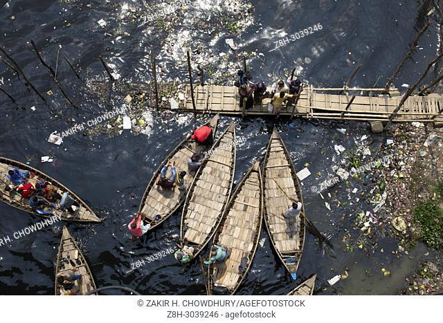 DHAKA, BANGLADESH - APRIL 17 : Bangladeshi commuters use boats to cross the Buriganga River in Dhaka, Bangladesh on April 17, 2018.