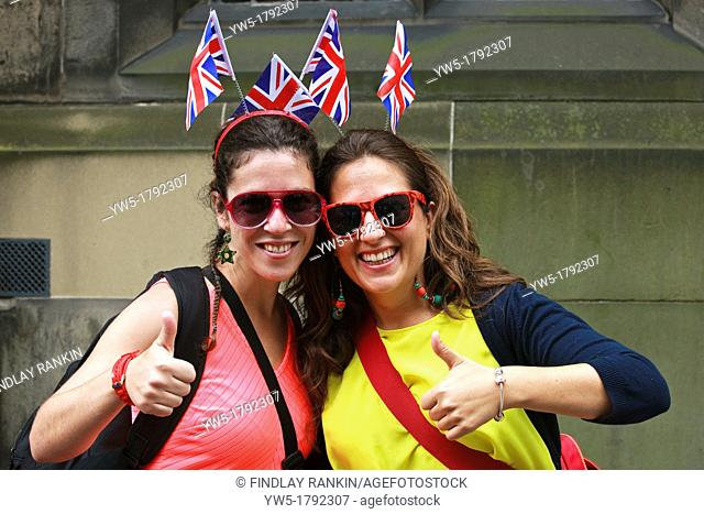 two Spanish girls, on holiday in Edinburgh, visiting the Edinburgh Fringe festival, wearing hair bands with the Union Jack flags thereon  Photo taken in High...