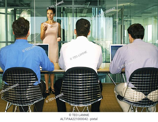 Woman standing in front of three men sitting side by side