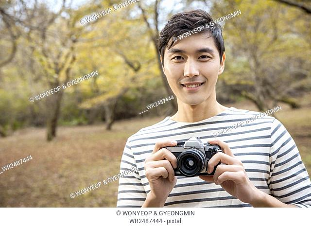 Portrait of young smiling man holding a camera in park