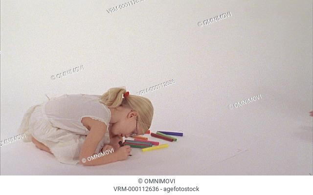 Girl drawing on floor, baby boy crawling