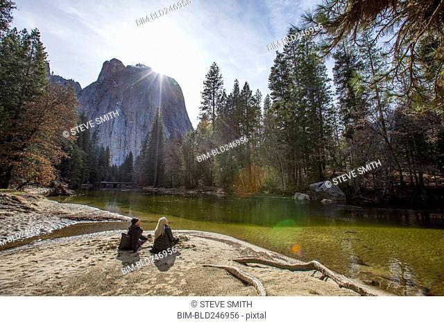 Caucasian couple sitting near river