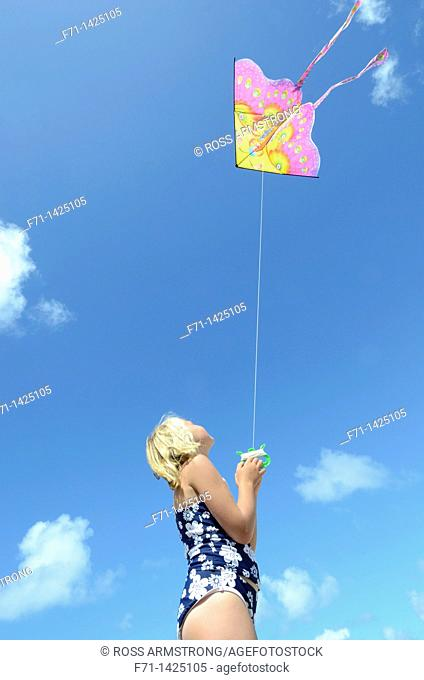 Six year old girl flying a kite at the beach  Mimiwhangata, Northland, New Zealand