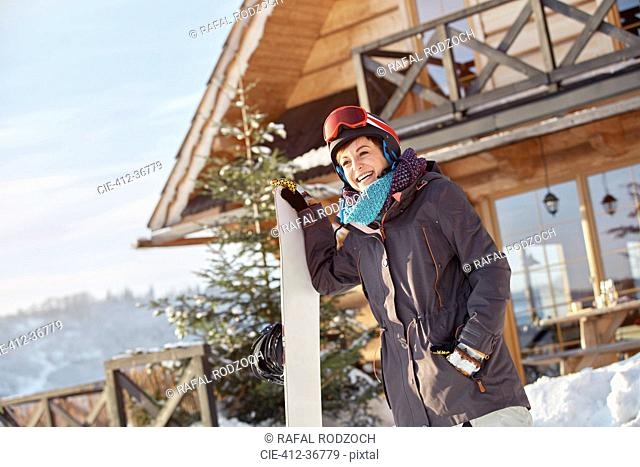 Smiling female snowboarder with snowboard outside sunny cabin