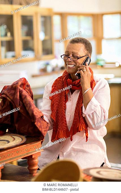 Older mixed race woman talking on telephone in home office