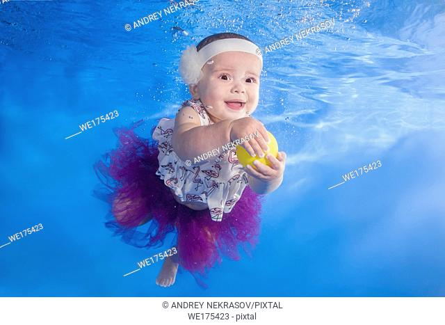 Little girl in a dress playing with a ball underwater in the pool