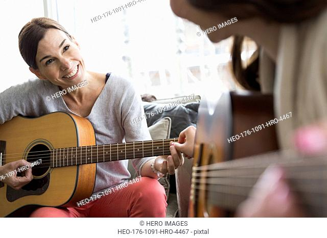 Mother and daughter playing guitar in living room
