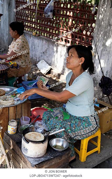 Myanmar, Yangon, Yangon. Woman at fast food stall cooking pancakes in Bogyoke, (formerly Scott) Market in Yangon in Myanmar