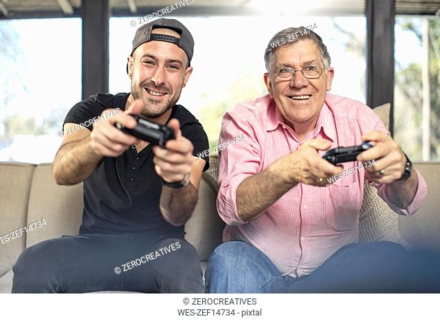 Happy grandfather and grandson playing video game on couch at home