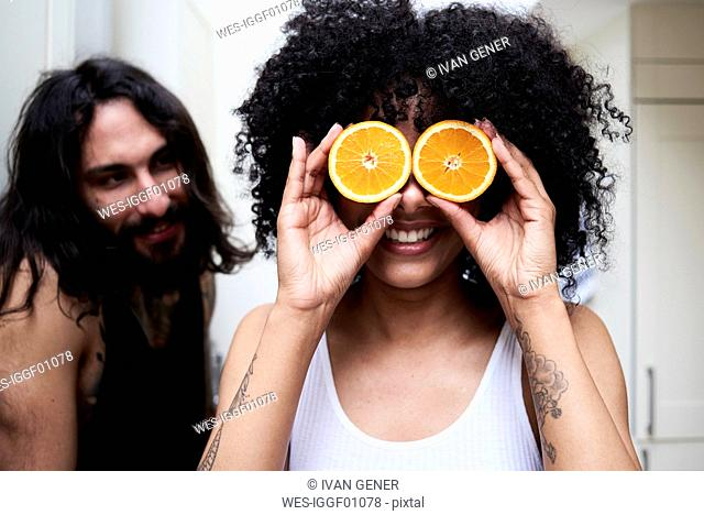 Happy young woman covering her eyes with oranges in kitchen