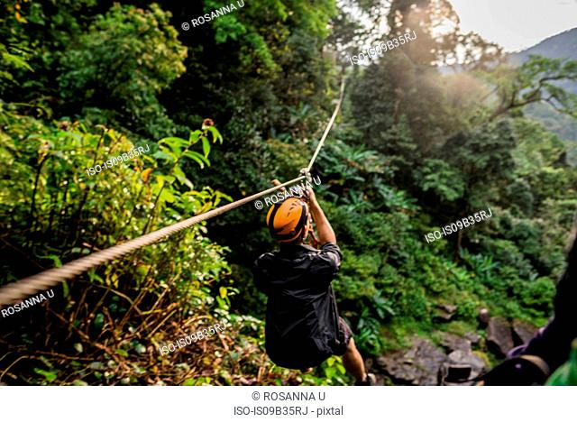 Man on zip wire in forest, Ban Nongluang, Champassak province, Paksong, Laos