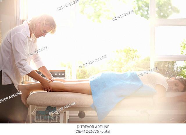 Masseuse massaging woman's legs