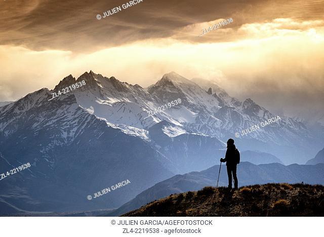 Silhouette of a trekker watching the mountains in the evening sun light. Nepal, Gandaki, Upper Mustang (near the border with Tibet). Model Released