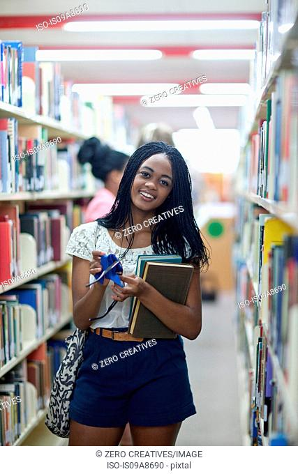 Female student in library holding books