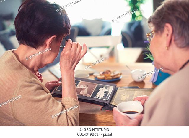 Over shoulder view of two senior women looking at photo album on table
