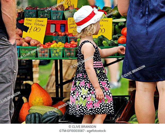 Little girl in summer dress at food market