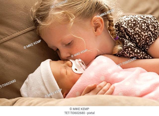Girl 2-3 embracing baby sister on sofa