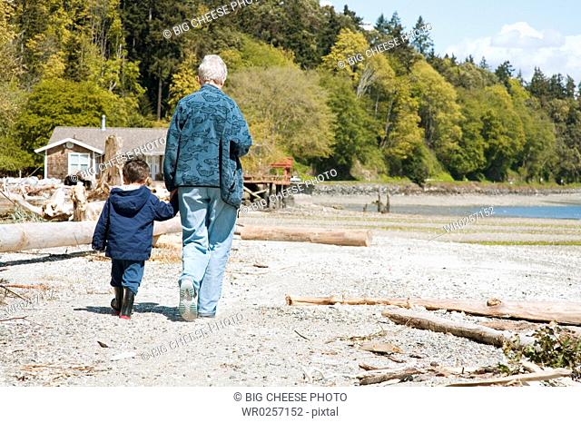 Grandmother and grandson walking on beach