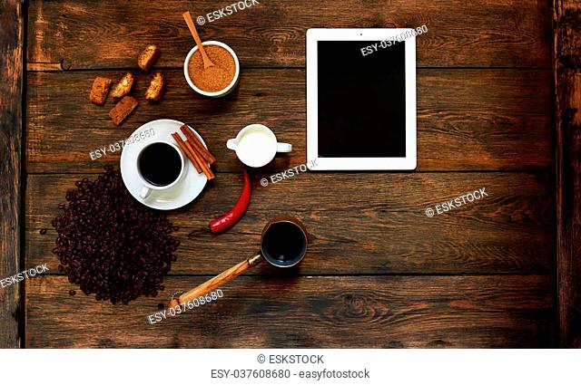 On a dark textural wooden table lies a tablet, is a cup of strong black coffee with milk, in a coffee Cezve residues