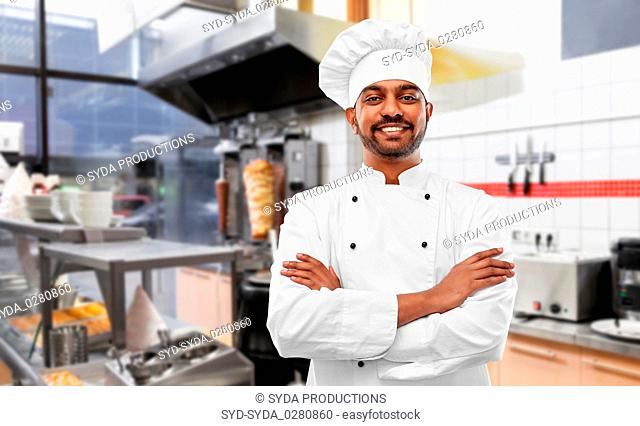 happy male indian chef in toque at kebab shop